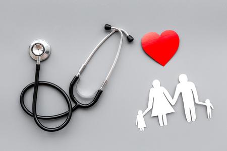 Retire o seguro de saúde para a família. Estetoscópio, papel e silhueta da família em fundo cinza Vista superior Foto de archivo - 91012407