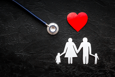 Take out health insurance for family. Stethoscope, paper heart and silhouette of family on black background top view copyspace