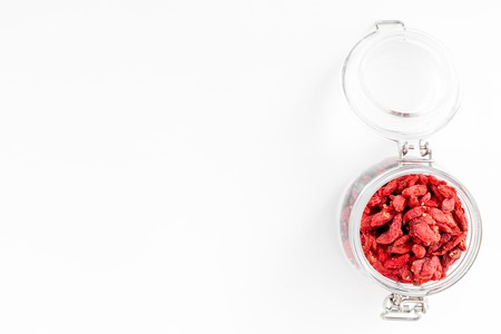 Dried goji berries in glass jar on white background top view copyspace Stock Photo