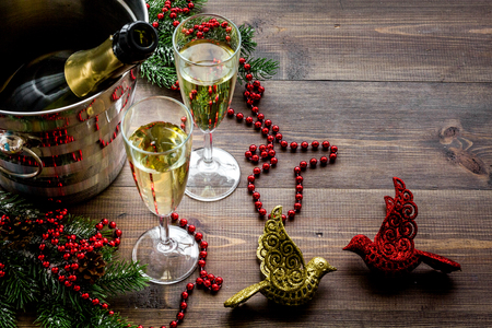 Champagne for celebrate new year. Glasses, bottle in bucket, spruce branch, decoration on wooden background copyspace