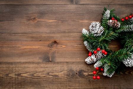 Weihnachtskranz gesponnen von den Fichtenzweigen mit roten Beeren auf Draufsichtspottbild des hölzernen Hintergrundes Standard-Bild - 90948768