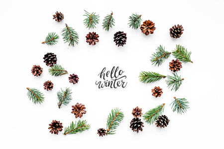 Hello Winter hand lettering. Winter pattern with spruce branch and cones on white background top view. Imagens - 89064603