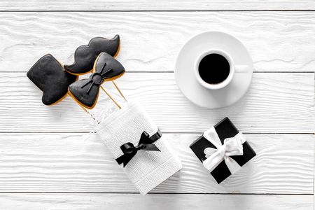 Birthday gift for men. Wrapped box, cookies in shape of black tie, mustache, hat. White wooden background top view. Stock Photo
