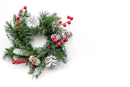 Christmas wreath woven of spruce branches with red berries on white background top view.