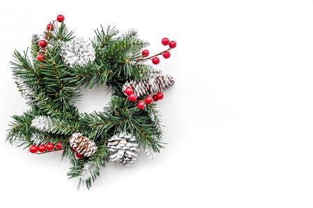Weihnachtskranz gesponnen von den Fichtenzweigen mit roten Beeren auf Draufsicht des weißen Hintergrundes. Standard-Bild - 89275403