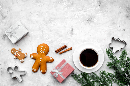 Coffee with gingebread cookies and gifts in christmas evening. Grey stone background top view.