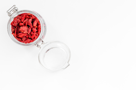 Dried goji berries in glass jar on white background top view.