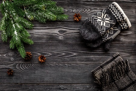 Cozy christmas evening. Knitten mittens and scarf on grey wooden background top view.