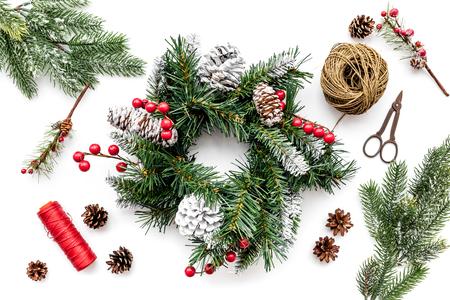 Machen Sie Weihnachtskranz. Gezierte Zweige, Kegel, Threads, Sciccors auf Draufsicht des weißen Hintergrundes. Standard-Bild - 89275610