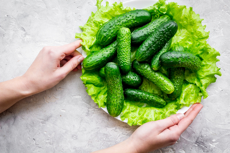 Hands take fresh cucumbers and salad. Grey background top view. Stock Photo