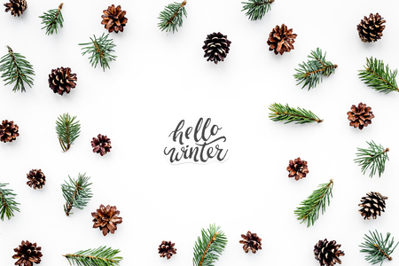 Hello Winter hand lettering. Winter pattern with spruce branch and cones on white background top view.
