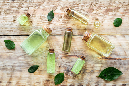 Skin care products with tea tree oil in bottles on rustic wooden background top view pattern.