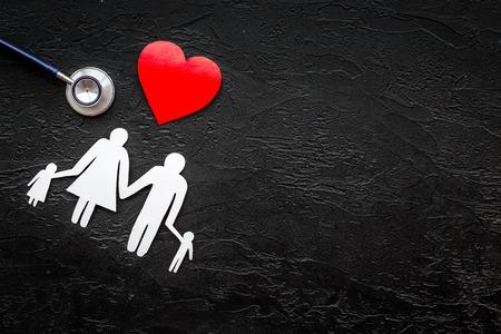 Retire o seguro de saúde para a família. Estetoscópio, coração de papel e silhueta da família na opinião superior do fundo preto. Foto de archivo - 89276062