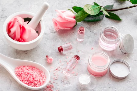 Make cosmetics with rose  oil. Mortar with rose petals and pestle on grey background. Stock Photo