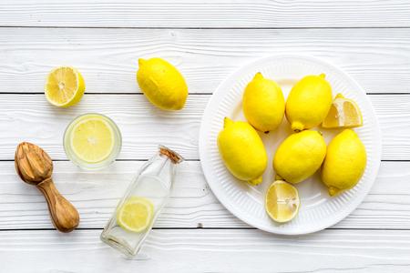 Make lemonade at home. Lemons, juicer, glass and bottle for beverage on white wooden background top view.