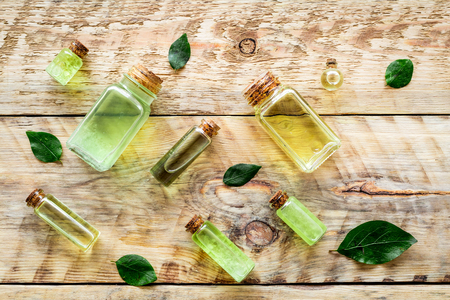 Skin care products with tea tree oil in bottles on rustic wooden background top view pattern. Stock Photo - 89247049