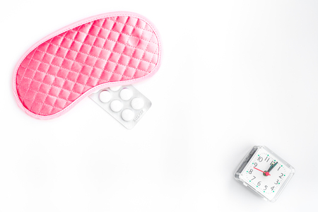 sleeping pills: Sleeping pills for insomnia near sleep mask and alarm clock on white background top view.