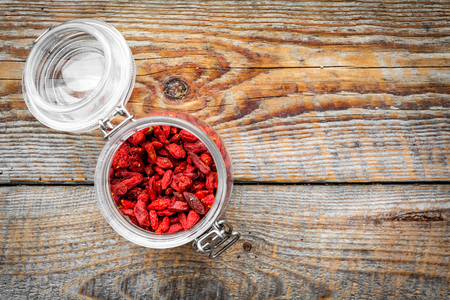 Dried goji berries in glass jar on wooden background top view.