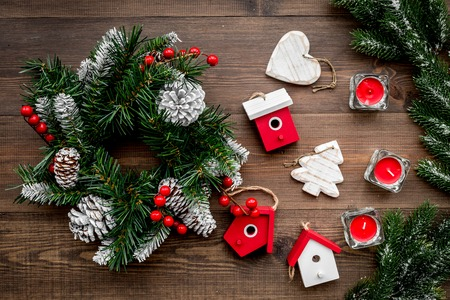 Christmas decorations. Wreath and toys on wooden background top view.
