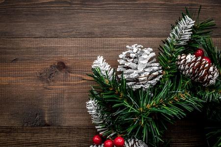 Weihnachtskranz gesponnen von den Fichtenzweigen mit roten Beeren auf Draufsicht des hölzernen Hintergrundes. Standard-Bild - 89247098