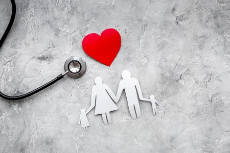 Take out health insurance for family. Stethoscope, paper heart and silhouette of family on grey background top view.