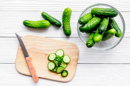 Cut fresh cucumbers on cutting board. Grey wooden background top view. Stock Photo