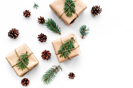 Gifts for new year wrapped in craft paper near spruce branches and cones on white background top view.