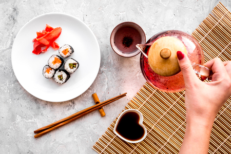 Hand pour the tea near plate with sushi roll with salmon and avocado on grey stone background top view.