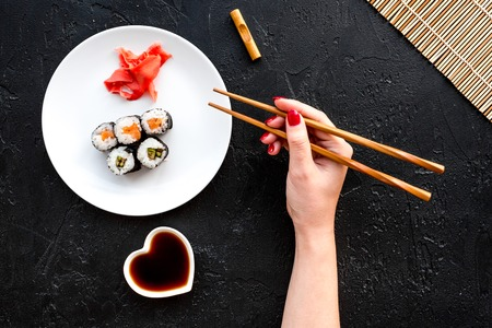 Hand takes sushi roll with salmon and avocado with chopstick. Black background top view. Stock Photo