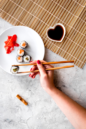 Hand takes sushi roll with salmon and avocado with chopstick. Grey stone and mat background top view.