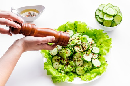 Hands pepper salad with fresh cucumbers and lettuce. White background.