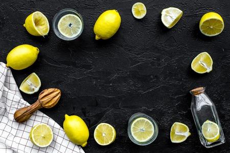 Make lemonade at home. Lemons, juicer, glass and bottle for beverage on black background top view.