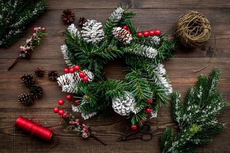 Machen Sie Weihnachtskranz. Gezierte Zweige, Kegel, Threads, Sciccors auf Draufsicht des hölzernen Hintergrundes. Standard-Bild - 89290241