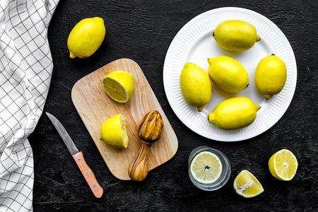 Make lemonade at home. Lemons, juicer, glass for beverage, knife, cutting board on black background top view.