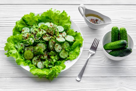 Salad with fresh cucumbers and lettuce near gravy boat. Grey wooden background.