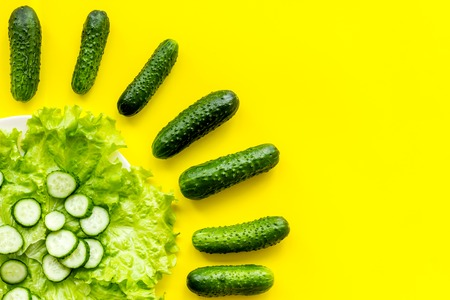 Pattern with fresh cucumbers and salad. Yellow background top view.