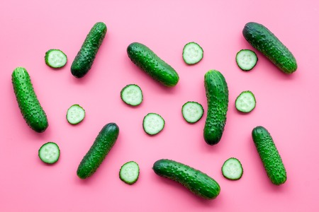 Pattern with fresh cucumbers. Pink background top view. Stock Photo