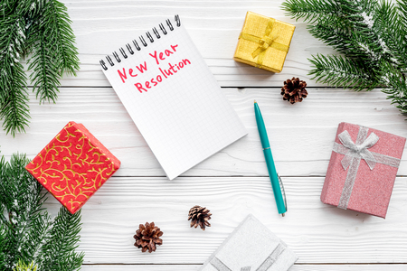 New year resolution. Notebook among gift boxes and spruce branch on white wooden background top view. Stock Photo