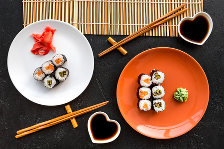 Sushi roll with salmon and avocado on plate with soy sauce, chopstick, wasabi on mat on black background top view. Stock Photo