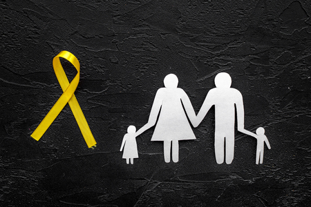Yellow ribbon for suicide and endometriosis awareness near paper silhouette of family on grey background top view.