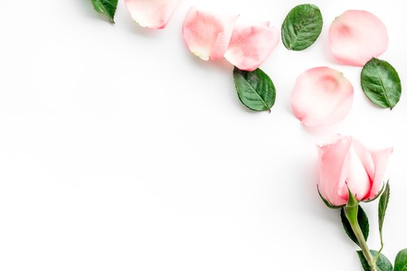 Pattern with rose oil cosmetics. Rose petals, spa salt on white background top view copyspace