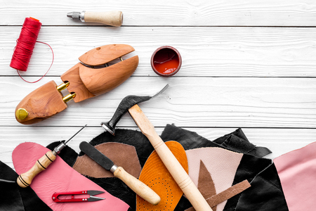 Shoemakers craft. Tools, wooden last, pieces of leather on white wooden background top view copyspace Foto de archivo