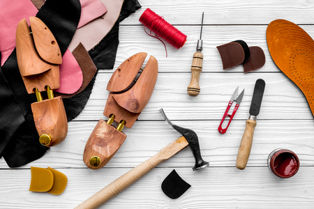 Shoemakers craft. Tools, wooden last, pieces of leather on white wooden background top view