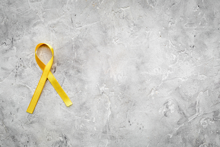 Yellow ribbon for suicide and endometriosis awareness on grey stone background top view copyspace Stock Photo
