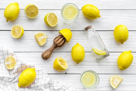 Make lemonade at home. Lemons, juicer, glass and bottle for beverage on white wooden background top view Stock Photo