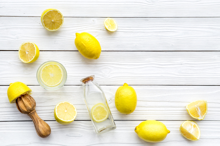 Make lemonade at home. Lemons, juicer, glass and bottle for beverage on white wooden background top view copyspace Stock Photo