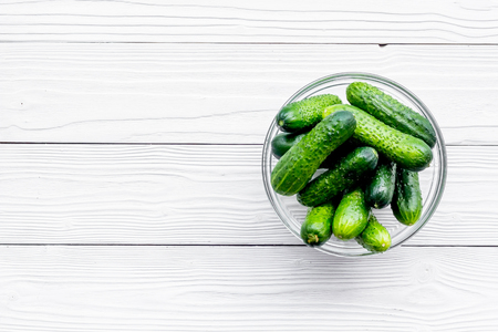 Fresh cucumbers at the bowl. Grey wooden background top view copyspace Stock Photo