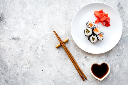 Sushi roll with salmon and avocado on plate with soy sauce, chopstick, wasabi on grey stone background top view copyspace Stock Photo