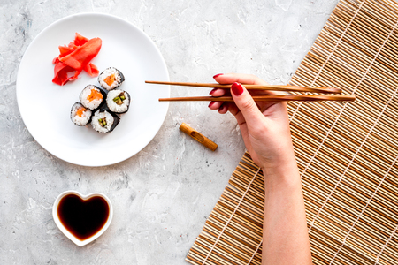 Hand takes sushi roll with salmon and avocado with chopstick. Grey stone and mat background top view