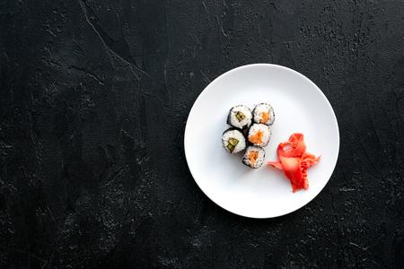 검은 색 바탕에 접시에 연어와 아보카도 스시 롤 상위보기 copyspace 스톡 콘텐츠